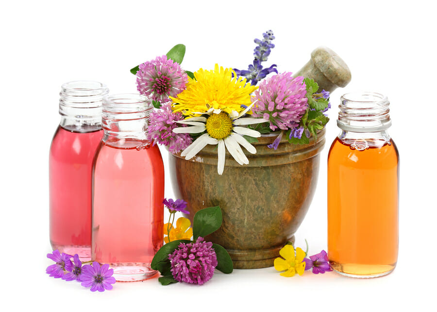 Mortar with fresh flowers and essential oil isolated on white background